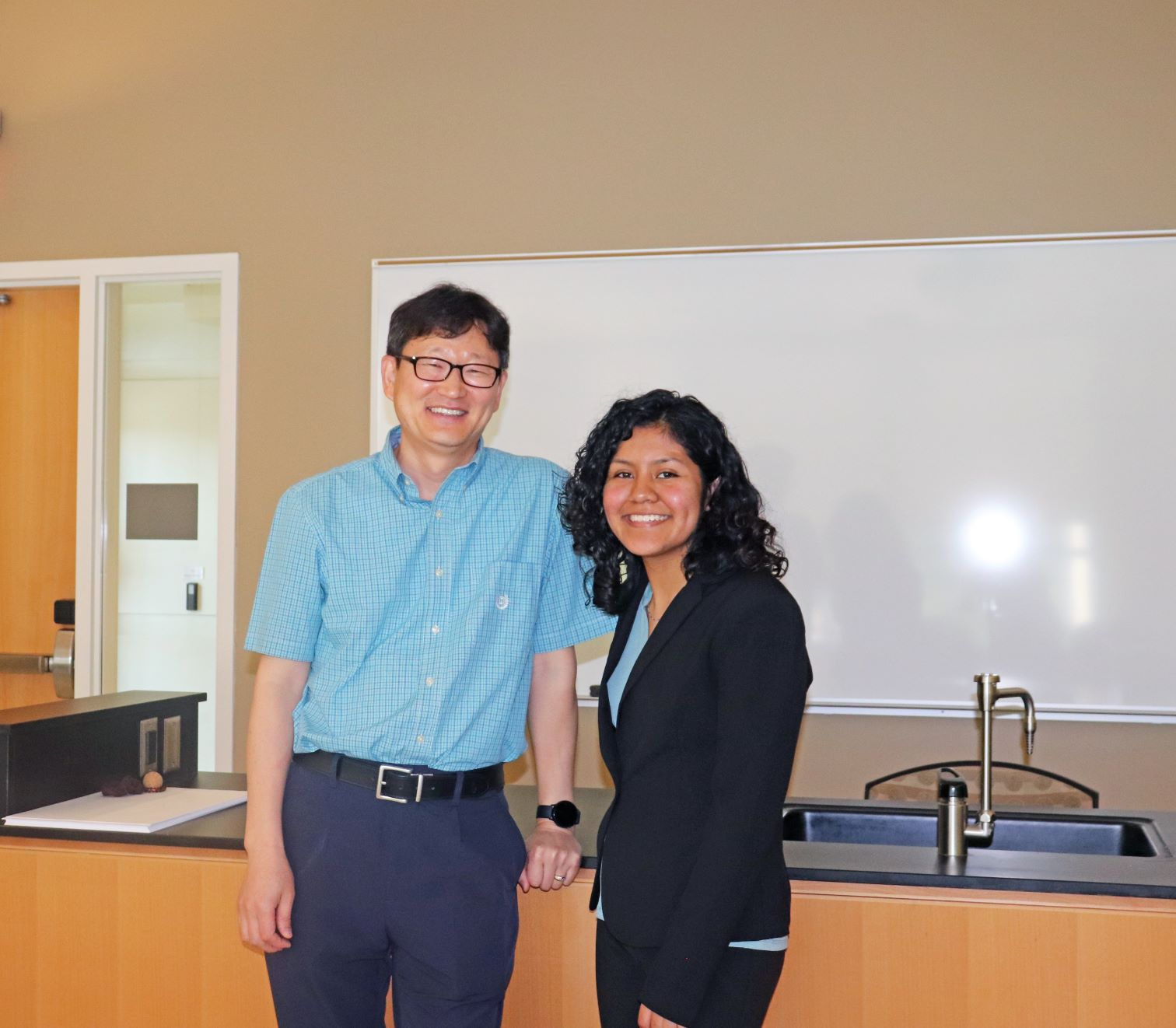 Assistant Professor of Chemistry Dr. Wooseok Ki mentored Dianareli Dolores during her STEM research. Both pose for the camera with smiles at the Research and Engineering Apprenticeship (REAP) Symposium.