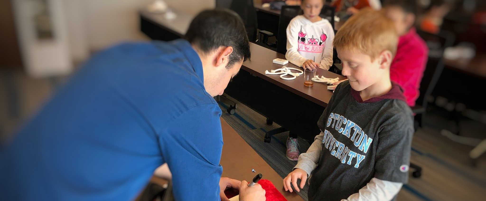 "Magician Chad Juros shows Kevin Nugent a magic trick while other alumni and their families practice during the Nov. 10, 2018 ""Second Saturdays in Atlantic City."""