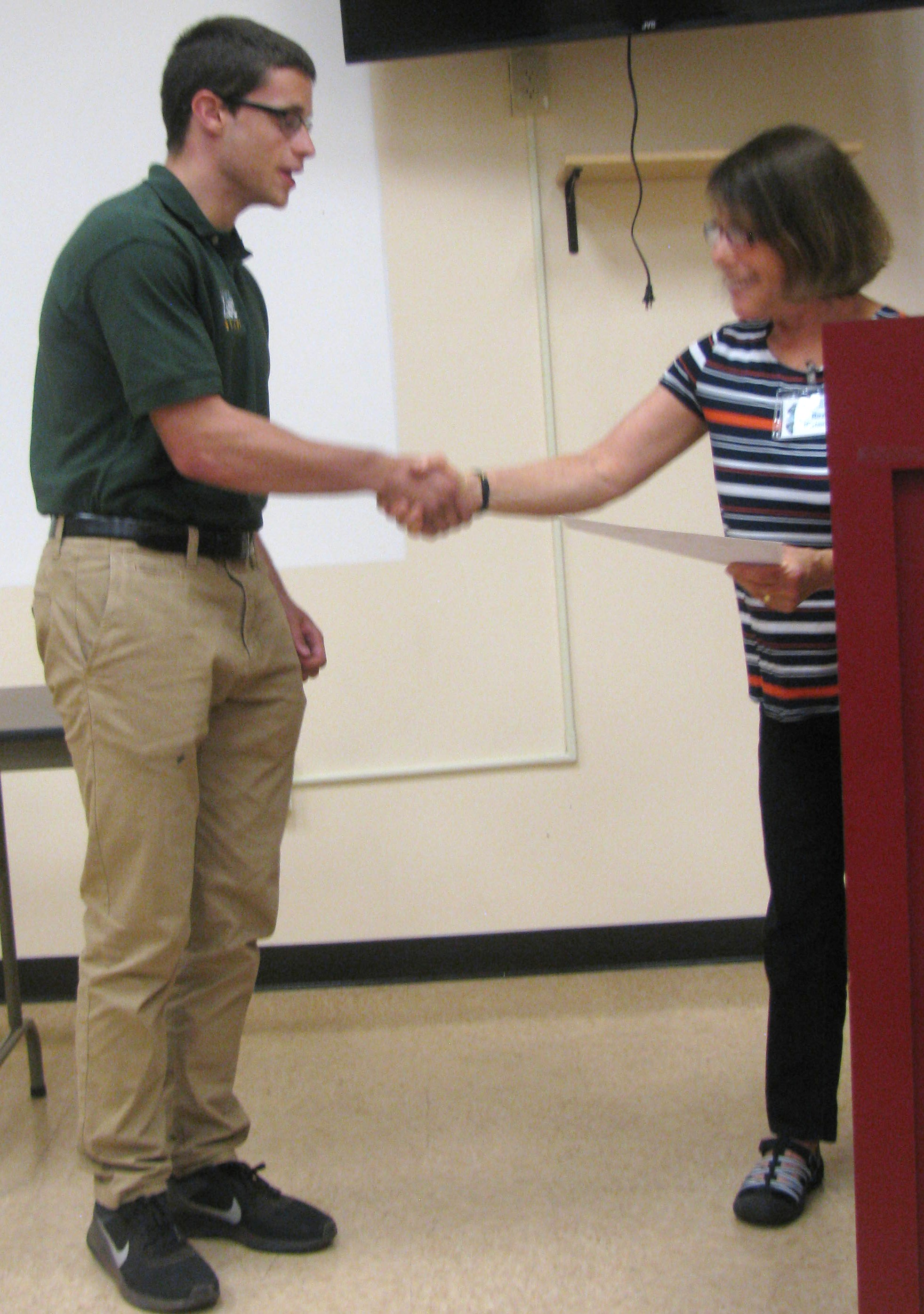 Alexander Melchiore receives the James F. Akers Memorial Conservation Scholarship from AAS member Roz Herlands. Photo credit: Charles Herlands
