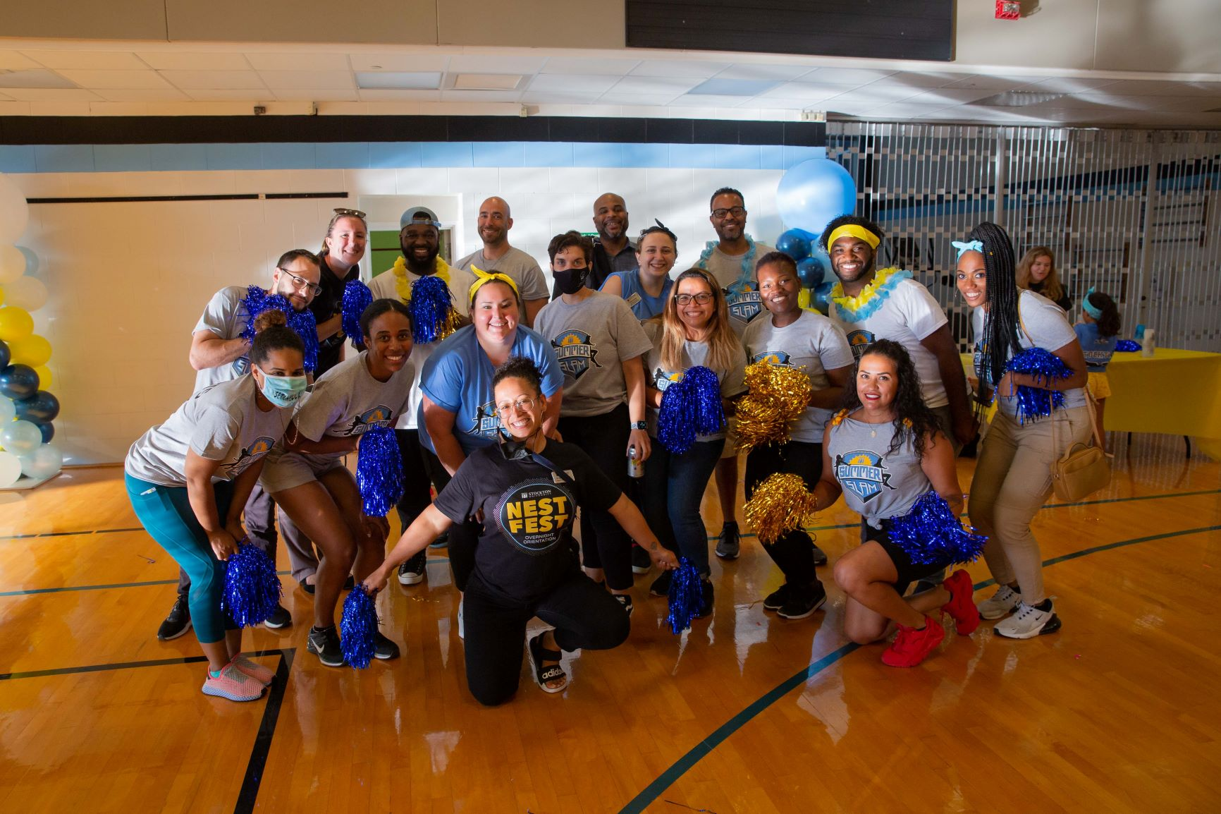 Staff members from various departments at Stockton University pose with big smiles for the camera during the Summer Slam event, part of Stockton's new overnight orientation experience called Nest Fest.