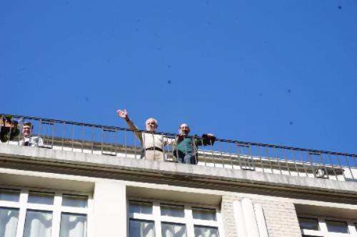 Holocaust survivor Daniel Kochavi waves from balcony.