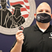 Jason Babin, director of the Office of Military and Veteran Services,  holds up a Stockton University challenge coin.