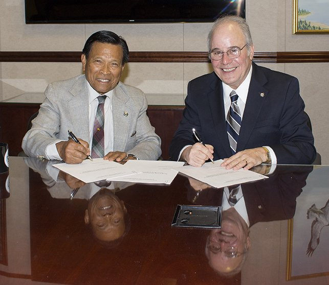 Cenon Jacob and President Harvey Kesselman sign gift agreement.