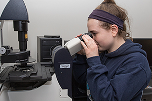 Image of student looking through the Leica Microsystems Microscope