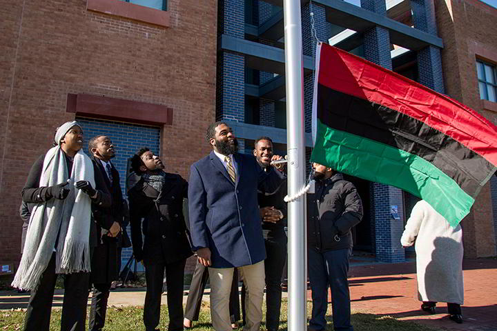The Unified Black Students Society raises the Pan-African Flag, a symbol of heritage and dignity.