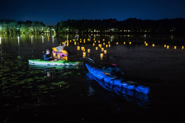 Paper lanterns with messages to loved ones lost to cancer float on Lake Fred under the moonlight during Kappa Sigma's Light Up Lake Fred benefit for the Ulman Cancer Fund for Young Adults.