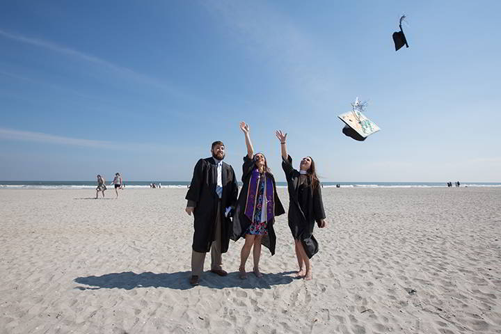 Ospreys toss their caps to the sky on the beach in a celebratory moment after Commencement in Boardwalk Hall