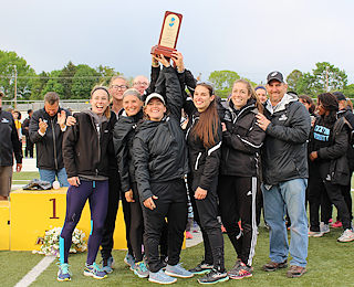 Stockton's women's track & field team celebrates  after winning the NJAC Championship in May.
